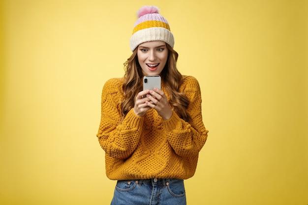 Mulher atraente e elegante espantada receber mensagem smartphone promoção incrível pronto para fazer compras online sorrindo emocionado e animado visor do telefone móvel, posando de fundo amarelo