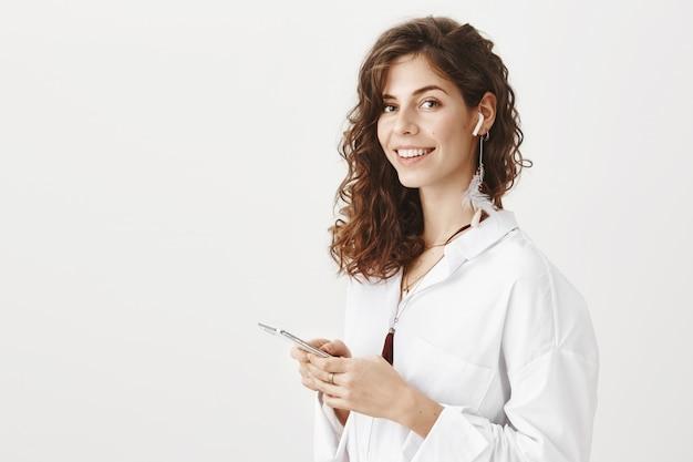 Mulher atraente e elegante ouvindo música em fones de ouvido sem fio, segurando um smartphone