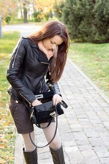 Mulher atraente e elegante procurando as chaves na bolsa enquanto está no caminho