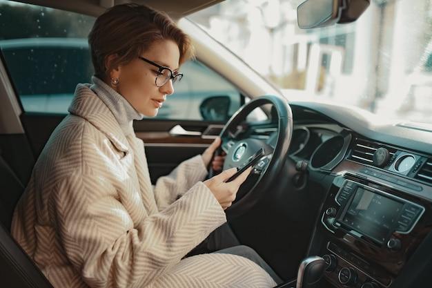 Mulher atraente e elegante sentada no carro, vestida com um casaco estilo inverno e óculos, usando telefone inteligente