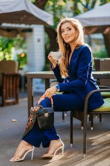 Mulher atraente e elegante vestida com um elegante terno azul, sentada à mesa no café, bebendo uma xícara de cappuccino