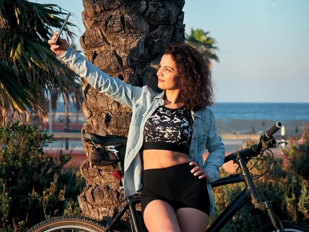 Mulher atraente e em forma no sportswear, fazendo uma selfie enquanto andava de bicicleta em um parque