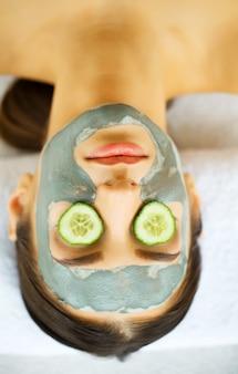 Mulher atraente e engraçada com máscara no rosto no spa