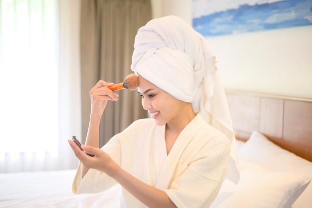 Mulher atraente e feliz em roupão branco aplicando maquiagem natural com pincel de pó cosmético