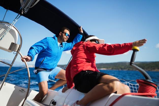 Mulher atraente e forte navegando com seu barco à vela