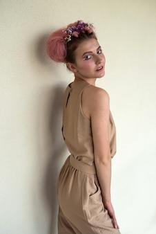 Mulher atraente e glamourosa em roupas bege contra a parede com maquiagem fashion