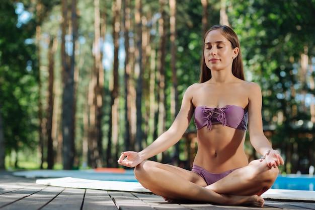Mulher atraente e magra de cabelos escuros fazendo ioga ao ar livre perto da grande piscina externa