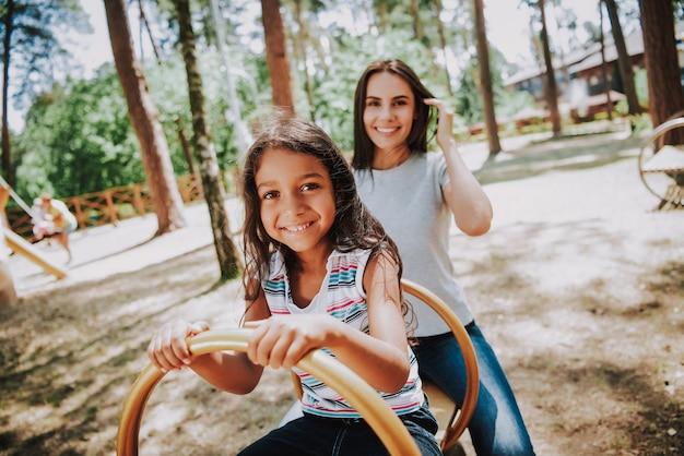 Mulher atraente e menina no playground