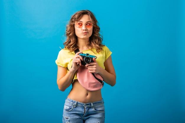 Mulher atraente e pensativa posando com uma câmera fotográfica vintage tirando fotos vestida com uma roupa colorida de verão moderno, isolada no fundo azul do estúdio