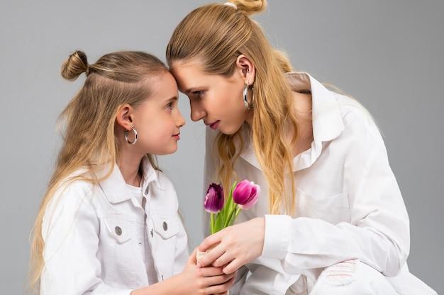 Mulher atraente e resoluta conectando a testa com a irmã mais nova enquanto apresenta flores