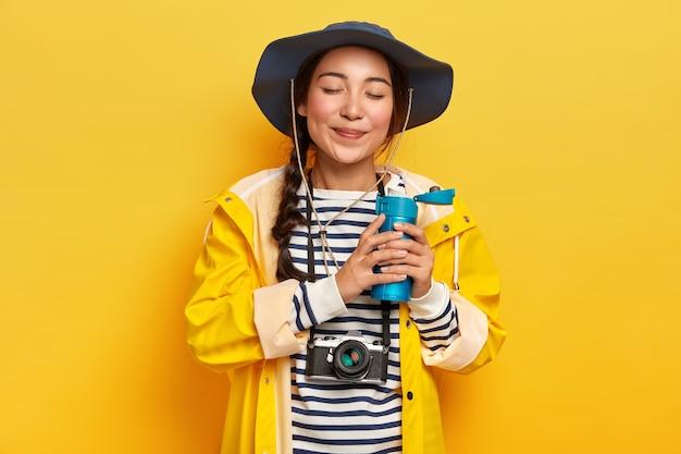 Mulher atraente e satisfeita com pigtail, bebe café quente ou chá do frasco, usa roupas impermeáveis casuais, câmera retro pendurada no pescoço, gosta de aventuras e viagens