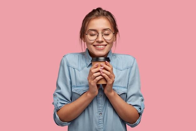 Mulher atraente e satisfeita segurando café para viagem