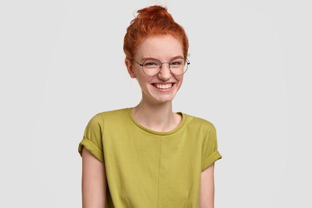 Mulher atraente e sensual dá risada, ri de história engraçada, tem cabelo ruivo penteado em coque, usa óculos óticos, modelos contra parede branca, parece simpática e despreocupada. conceito de felicidade