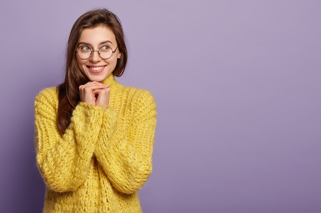 Mulher atraente e sonhadora e satisfeita segura as duas mãos embaixo do queixo, olha para o lado e fica feliz