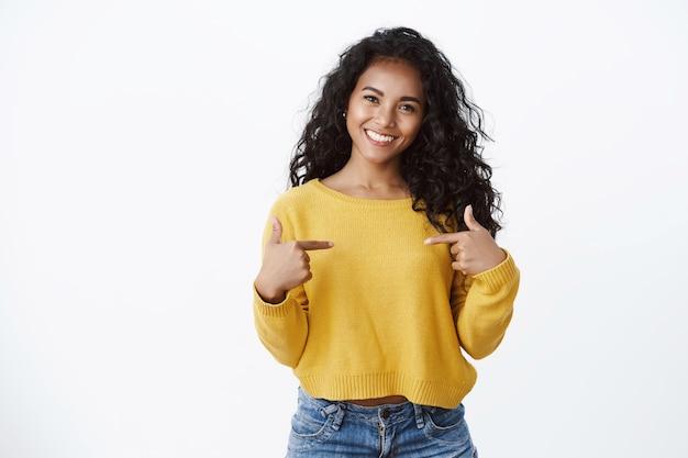 Mulher atraente e sorridente em um suéter amarelo, apontando para si mesma com orgulho, exibindo-se orgulhosamente, gabando-se de sua própria conquista, em pé na parede branca