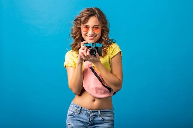 Mulher atraente e sorridente feliz posando com uma câmera fotográfica vintage tirando fotos vestida com uma roupa colorida de verão moderno, isolada no fundo azul do estúdio