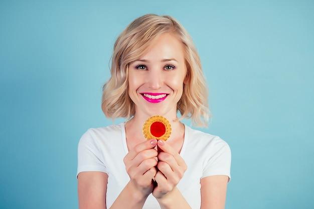 Mulher atraente e sorridente loira com maquiagem e batom nos lábios cor fúcsia mantém um biscoito de alto teor calórico na mão no estúdio sobre um fundo azul