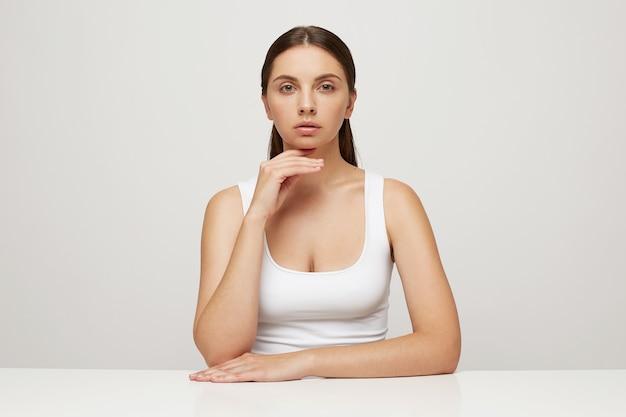 Mulher atraente e terna com pele perfeita e saudável se senta à mesa, com uma mão cruzada e a outra sob o queixo