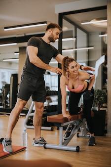 Mulher atraente e um personal trainer com musculação na academia