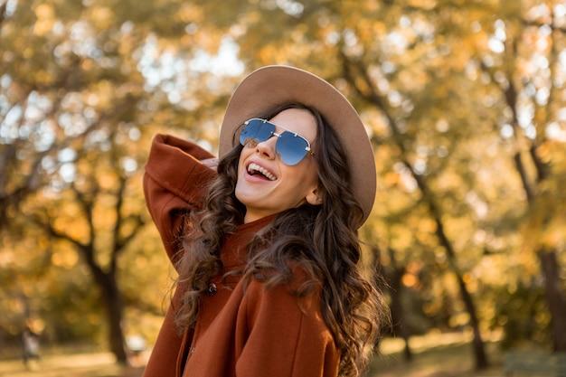 Mulher atraente, elegante e sorridente, com cabelo encaracolado andando no parque da rua, vestida com um casaco marrom quente na moda do outono, estilo de rua usando chapéu e óculos escuros