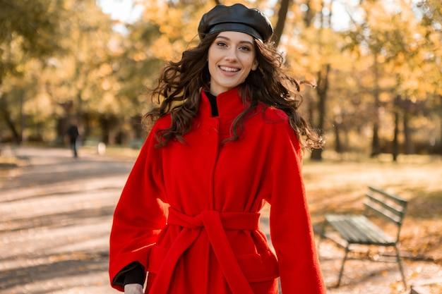 Mulher atraente, elegante e sorridente, com cabelos cacheados caminhando no parque, vestida com um casaco vermelho quente na moda do outono, estilo de rua, usando um chapéu boina