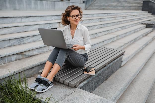 Mulher atraente elegante e sorridente de óculos trabalhando digitando no laptop