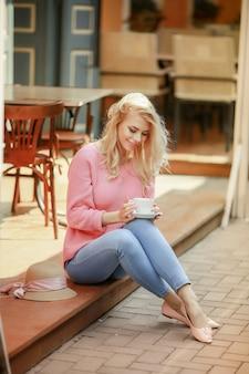Mulher atraente em clima romântico, sorrindo em felicidade, sentado à mesa, vestindo jaqueta rosa
