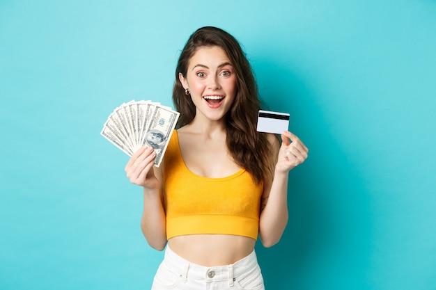 Mulher atraente em forma com roupa de verão, mostrando dinheiro de notas de dólar e cartão de crédito de plástico, sorrindo espantada, de pé contra um fundo azul.