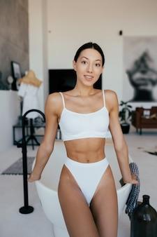 Mulher atraente em lingerie posando perto do banho. garota posando para a câmera