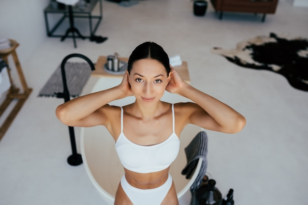 Mulher atraente em lingerie posando perto do banho
