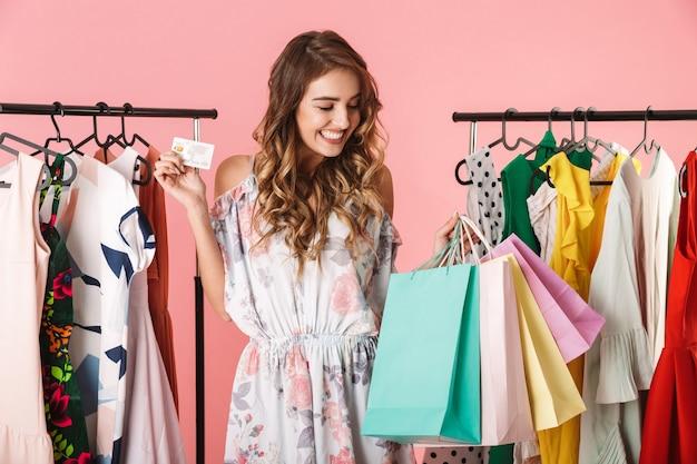 Mulher atraente em pé perto do guarda-roupa, segurando sacolas de compras coloridas e cartão de crédito isolado em rosa