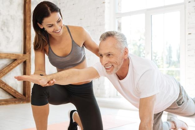 Mulher atraente em pé perto do visitante e apoiando-o durante o treinamento