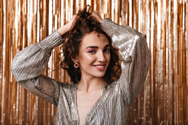 Mulher atraente em roupa brilhante tocando seu cabelo encaracolado em fundo dourado