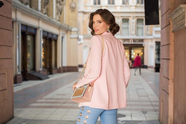 Mulher atraente em roupa elegante andando pela cidade, moda de rua, tendência primavera-verão, sorrindo, humor feliz, vestindo blusa e jaqueta rosa, vista de trás, elegância
