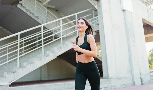Mulher atraente em roupas esportivas correndo ao ar livre em ambiente urbano.