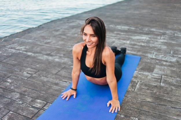 Mulher atraente em roupas esportivas fazendo exercícios de alongamento deitada em uma esteira na praia
