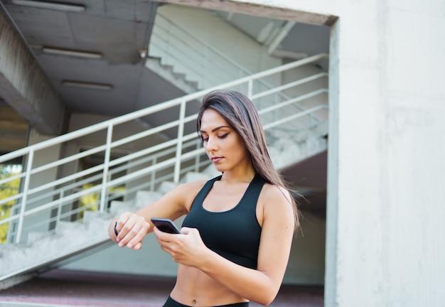 Mulher atraente em roupas esportivas usa relógio inteligente ao ar livre em ambiente urbano
