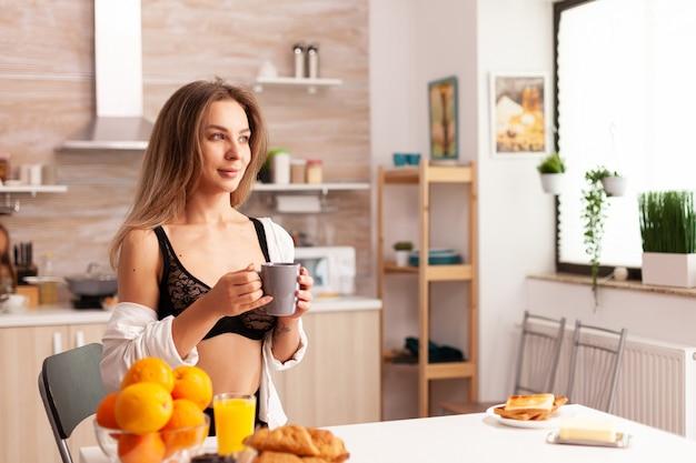 Mulher atraente em roupas íntimas durante o café da manhã na cozinha de casa, depois de acordar.