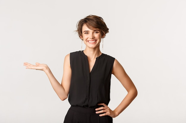 Mulher atraente em roupas pretas casuais, levantando a mão, segurando seu produto ou logotipo na palma da mão, sorrindo para a câmera feliz, branca.