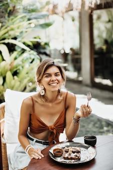 Mulher atraente em sutiã marrom sorri amplamente e come waffle saboroso com sorvete e calda de chocolate