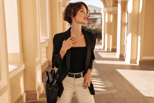 Mulher atraente em top preto, jaqueta e calça branca com cinto posando do lado de fora. mulher de cabelos ondulados com bolsa e óculos parece longe na cidade.