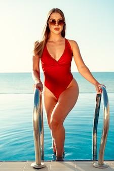 Mulher atraente em traje de banho vermelho e óculos de sol saindo da piscina