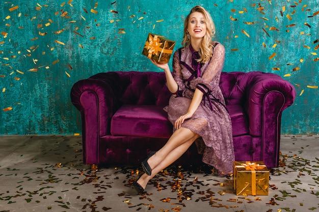 Mulher atraente em um elegante vestido de noite violeta elegante, sentada no sofá de veludo com presentes