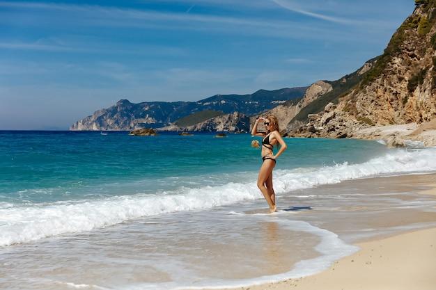 Mulher atraente em um maiô em pé na praia