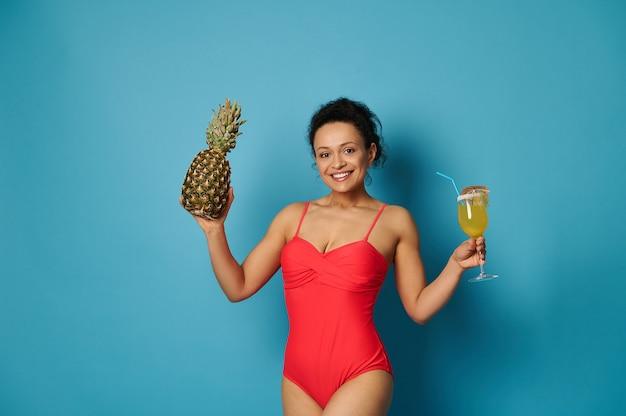 Mulher atraente em um maiô vermelho posando com um copo de coquetel e um abacaxi nas mãos