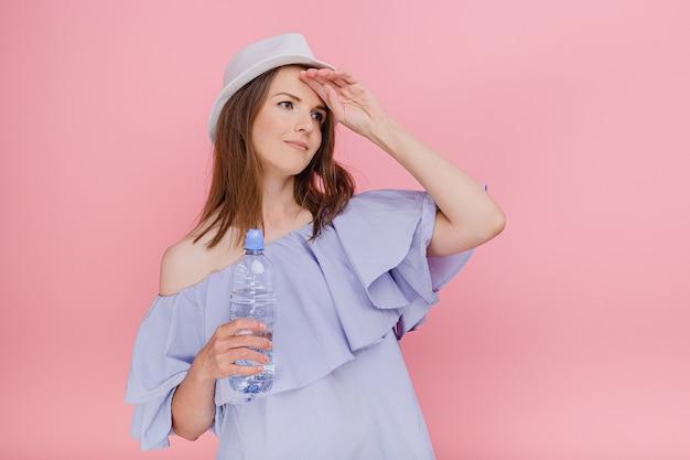Mulher atraente em um top estiloso com ombros nus segurando uma garrafa de água doce na mão quente dia de verão sorrindo, tendo bom humor, sentindo cansaço, olhar para fora