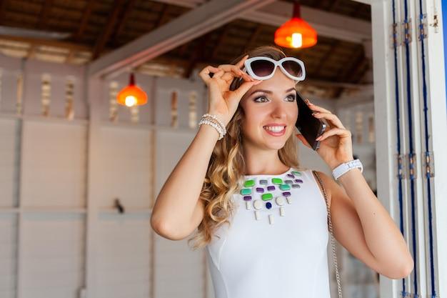 Mulher atraente em um vestido branco em um café de verão com óculos de sol falando ao telefone