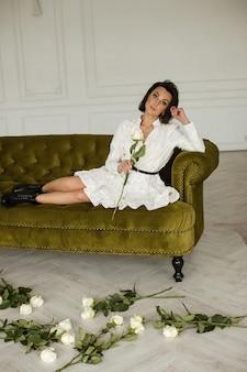 Mulher atraente em um vestido branco posa para a câmera no sofá com um monte de rosas ao redor