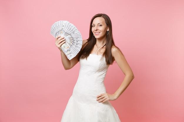 Mulher atraente em um vestido branco segurando um pacote de muitos dólares, dinheiro vivo