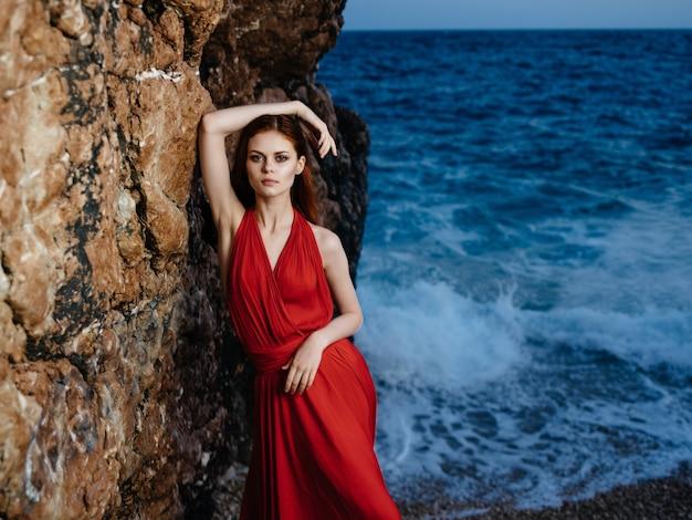 Mulher atraente em um vestido vermelho perto das rochas do oceano posando